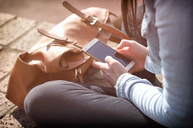 Chica sentada en el suelo con bolso y móvil