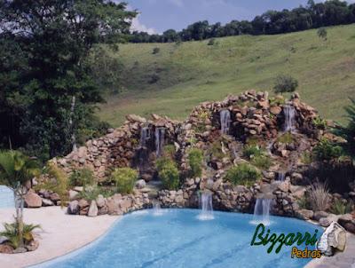 Execução da cascata de pedra na piscina com pedras ornamentais com o lago com a cachoeira de pedra encostada na piscina e a execução do paisagismo.