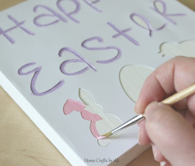 painting wood block with happy easter stencil made of cardstock and cut with cricut machine