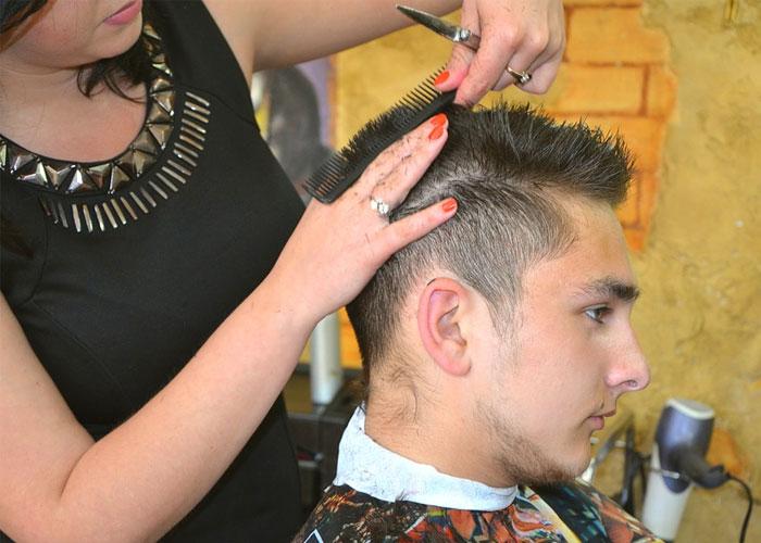 mulher cortando cabelo do homem no salao de beleza