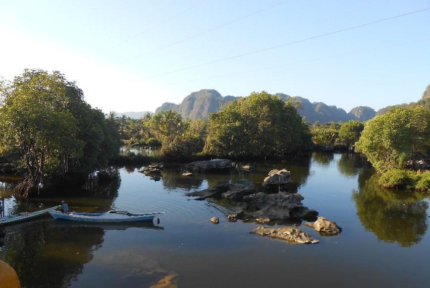 Perahu melaju dengan perlahan menyusuri sungai yang kadangkala harus berkelok-kelok mengikuti jalur yang ada.