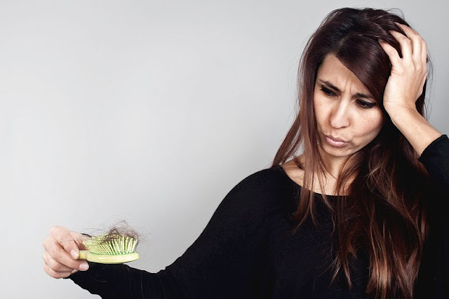 Young women losing hair on hairbrush