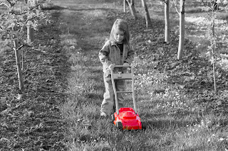 Little girl pushing fake lawn mower