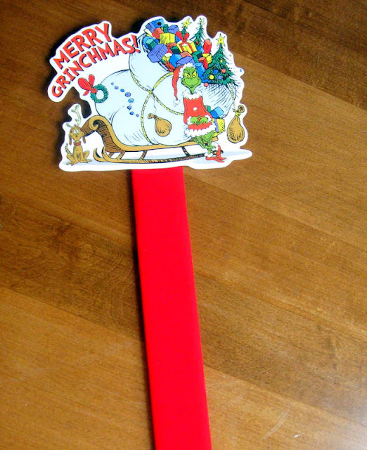 A  grinch gift tag on the end of a red paint stick to  be used as a marker in a homemade Grinch party advent calendar