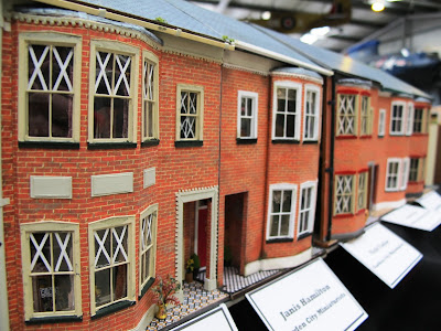 Row of miniature terrace houses with paper tape on the windows.