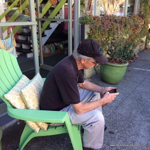man relaxing at exterior of rockflowerpaper shop in San Anselmo, California
