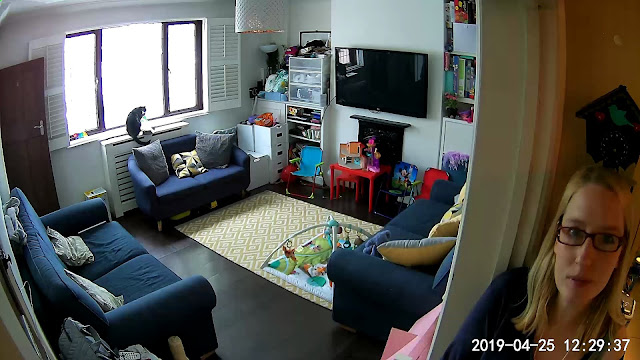 Still frame image from Neos SmartCam showing a front room and person with date stamp