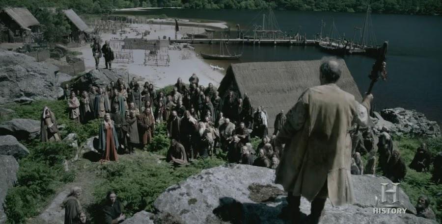 Fotograma de la serie Vikings, en la que se ve una asamblea, donde la gente está reunida y un hombre con un cayado está de pie sobre una roca.