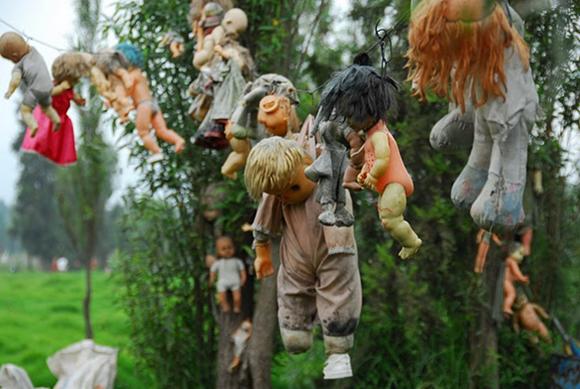 Bonecas penduradas em árvores