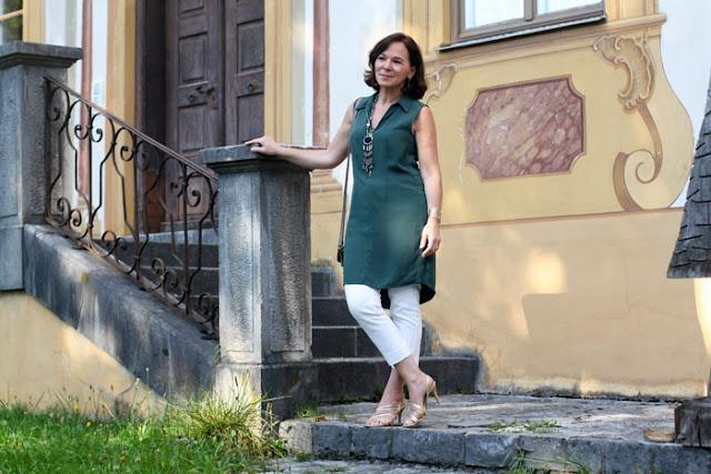Женщина за 50 в зеленой тунике, узких белых брюках и босоножках на каблуке