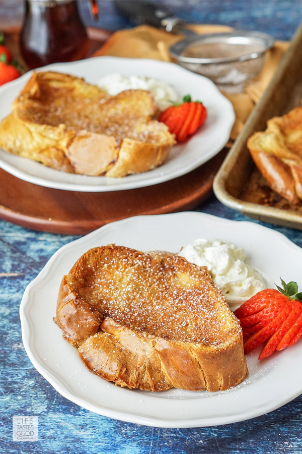 Breakfast table with creme brulee french toast on white plates with whipped cream and strawberries