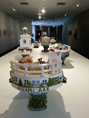 Selection of miniature wooden painted artist's arks on display in a gallery.