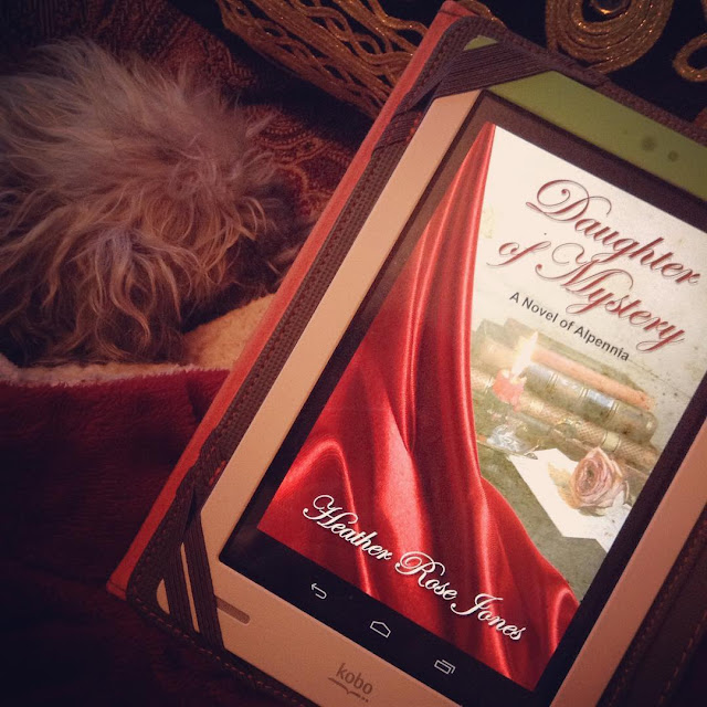 Murchie curls up in a red blanket cave beside a white Kobo with the cover of Daughter of Mystery on its screen. The cover features a red velvet drape across the bottom left hand corner, partway framing a pile of books, a rose, and a candle.