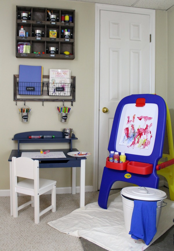 An organized kids art station including a painting station with a trash can with sheet and smock for easy setup and cleanup