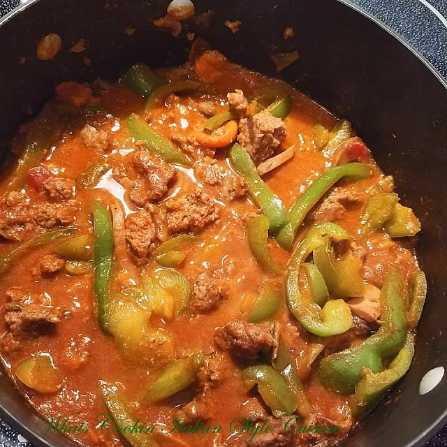 this is a pan of sausage , peppers and mushrooms simmering in a wine sauce using cabernet wine to make this rich tomato Italian sauce for a sandwich