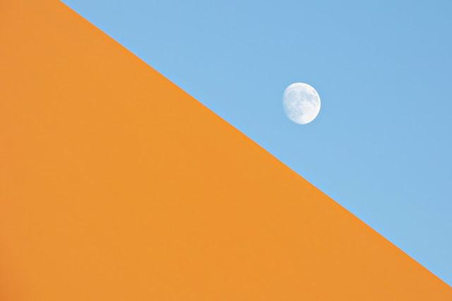 Vista de la lluna de dia al costat d'una gran duna del Sahàra