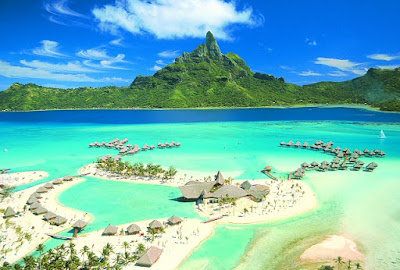 Vue aérienne d'un Atoll à  Tahiti, avec des bungalows sur pilotis.