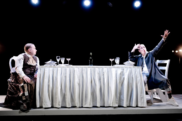 Actors Joakim Hagelin Adeby and Mette Marqvardsen on stage, seated across from each other at a long table set for a banquet, dressed in historical costumes and signing. Photographer: Urban Jörén