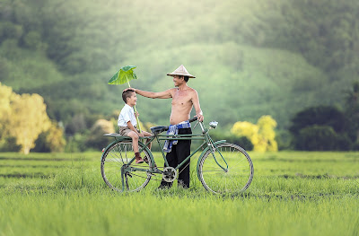 man with child on bike in cambodia