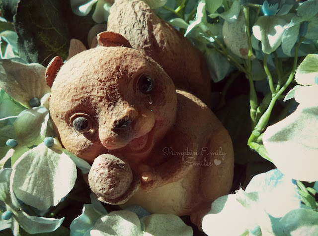 Tiny statue of a cute squirrel in a basket of fake flowers