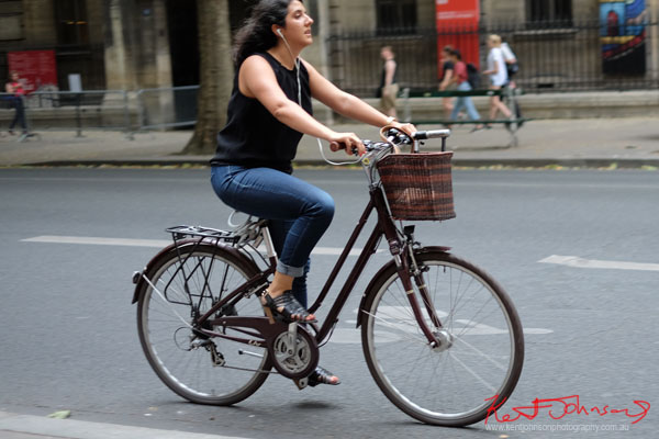 Woman in black singlet shirt, blue jeans and sandals riding a unisex bike with handlebar basket. Paris photos by Kent Johnson for Street Fashion Sydney.