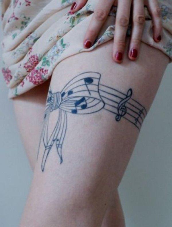 chica que se levata la faldita y vemos el tatuaje de un lazo hecho con pentagrama musical y notas