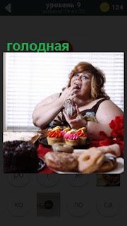 за столом сидит голодная женщина и ест сладости