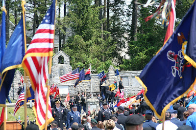 US and other colorful flags and military personnel in front of stone wall of 28th Division Shrine