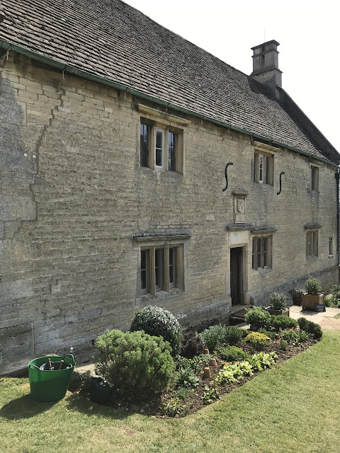 Exterior of a stone manor house, with tidy and flower boarders in front of the house