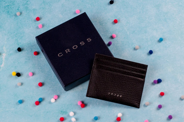 A presentation box with a black leather credit card holder resting on it with CROSS written in small metal writing