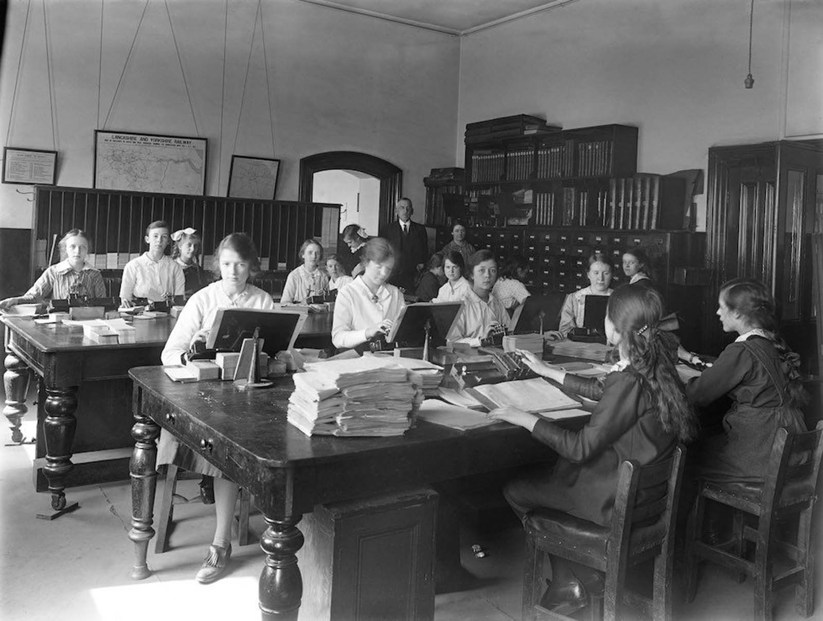 Office at the railway works in Horwich, Lancashire, England. During the First World War many male rail workers joined the army, so women were employed in their place, in a variety of roles including blacksmiths, welders and electricians. Most of the women in this office wear white blouses, but the blouses are more closely fitting than in the previous picture. Their hair is still worn up, though now more loosely, and one woman — at the card cabinets — has shoulder-length hair worn down, while another wears long braids. At least two younger women also have white bows in their hair. The woman in the left foreground shows a shorter skirt length and a leather shoe with a golfing-style flap. 1917.