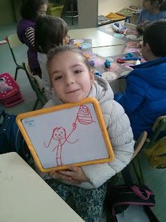 una niña se dibuja con una bandera en una pizarra
