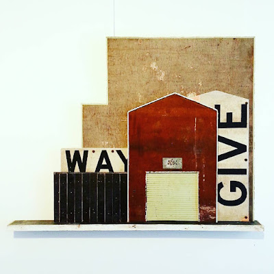 Assemblage art piece by Alex Asch, with various distressed boards making up a 2D view of old warehouse buildings.