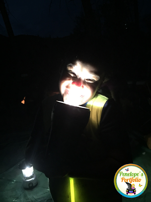 A boy holding a flashlight to light up his face in a fun way, at night while camping