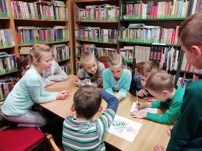 Dzieci siedząc przy stole, rozwiązują zadanie