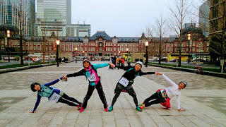 東京駅の前で4人手を繋いで組体操風のポーズ