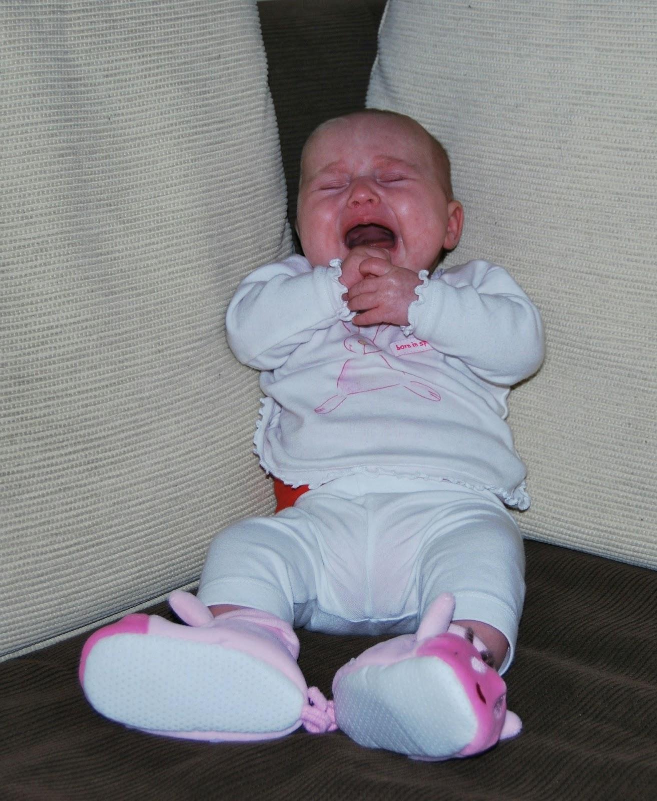 Baby sitzt auf Sofa und weint