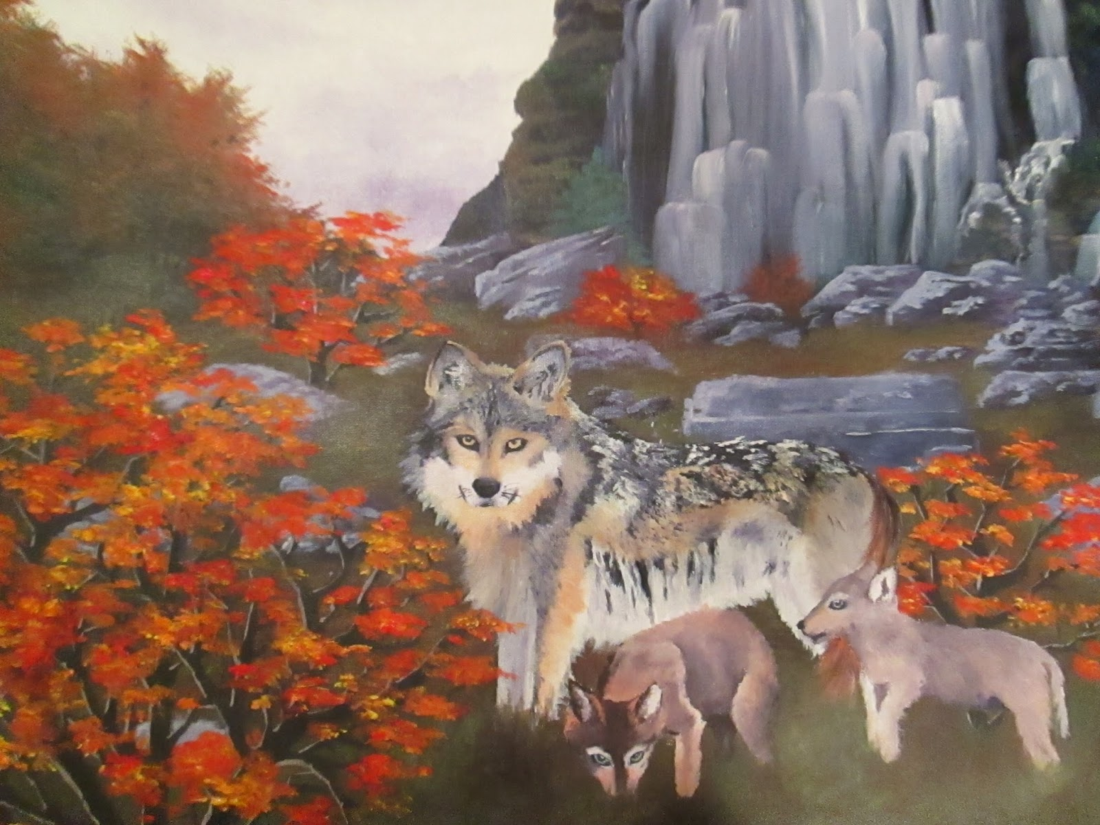 Three wolves by a waterfall