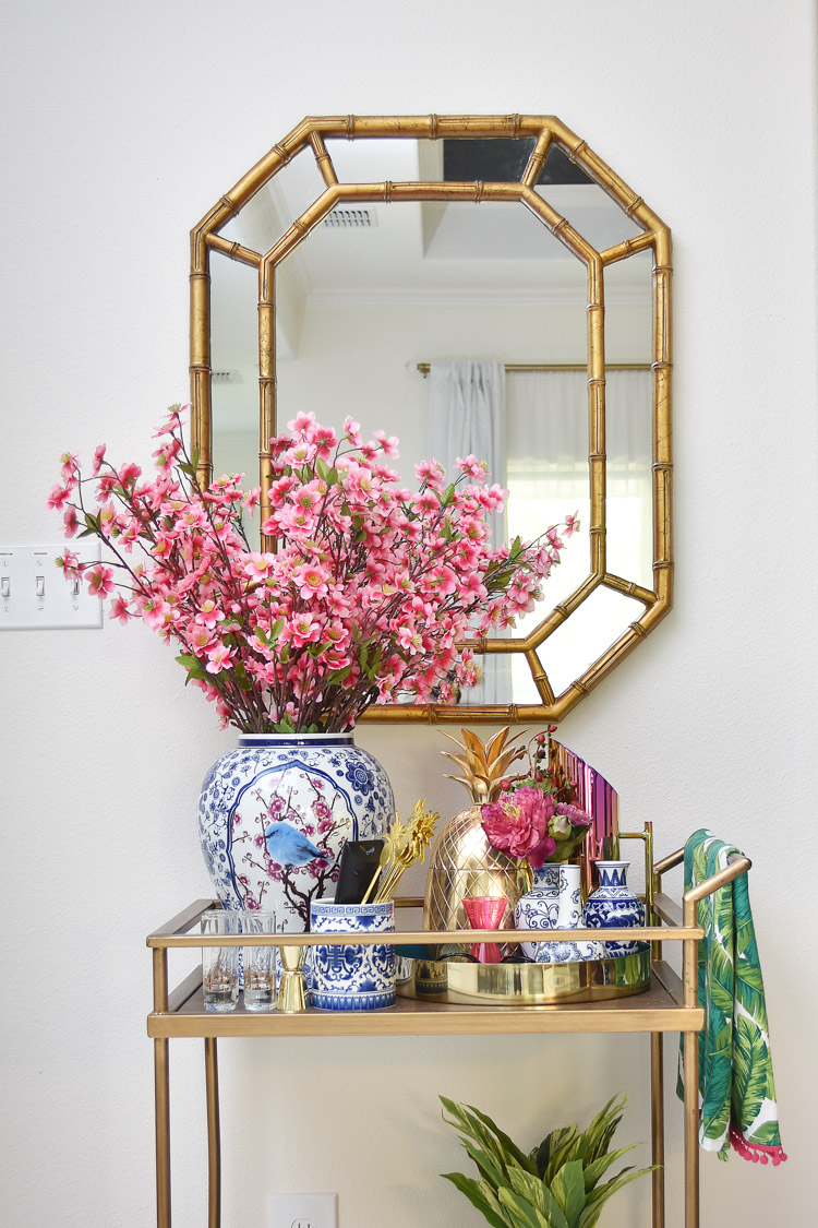 A colorful bar cart with chinoiserie and gold accents. Glam and fun!