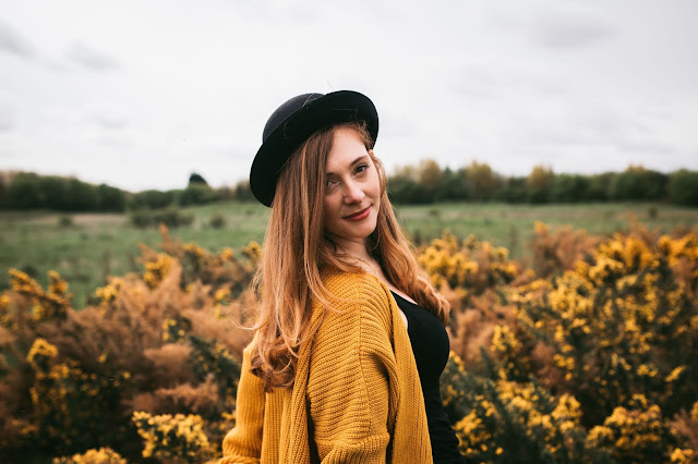 woman standing in front of yellow flowers in bowler hat and looking at the camera posing