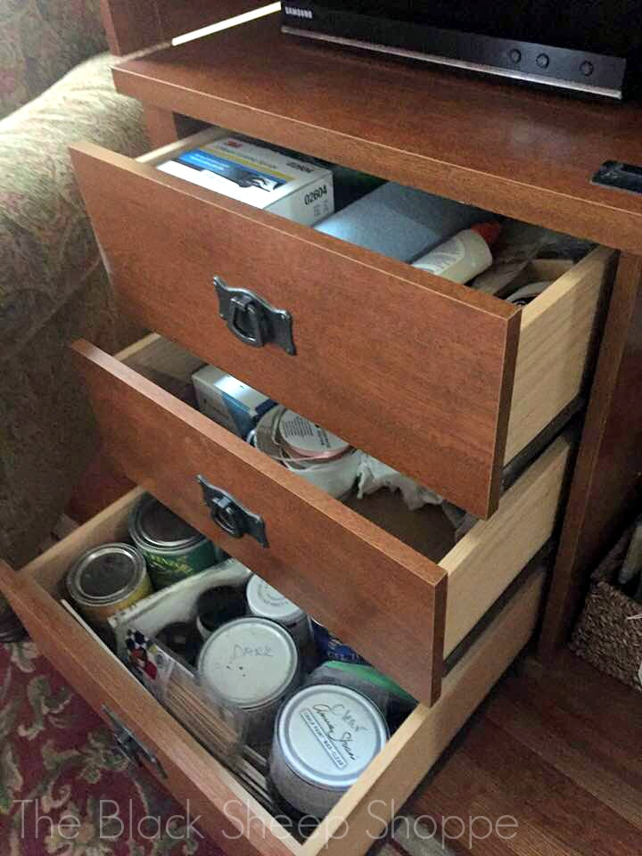 Paint supplies stored inside TV armoire