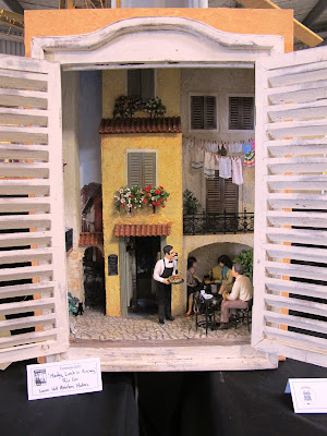 Cupboard with a one-twelfth scale miniature scene of a European courtyard with a waiter serving diners inside it