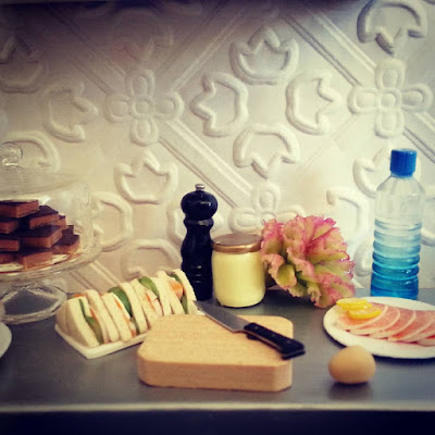 Modern miniature plates of cakes and sandwiches, with the sandwich components laid out on a metal bench top.