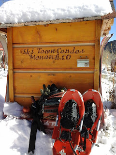 Set of snowshoes and pack leaning up against Ski Town Condos sign.