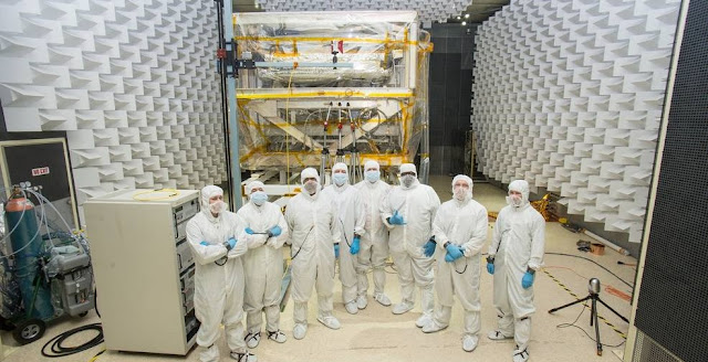 A team of engineers in special clean room suits at NASA Goddard. Seen from left to right: Andy Mentges, Nathan Block, Vaughn Nelson, Rob Houle, John McCloskey, Mark Branch, Rick Jones, Greg Jamroz. Credits: NASA/Chris Gunn
