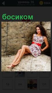 Среди огромных камней сидит девушка в платье с красным поясом босиком без обуви с улыбкой на лице