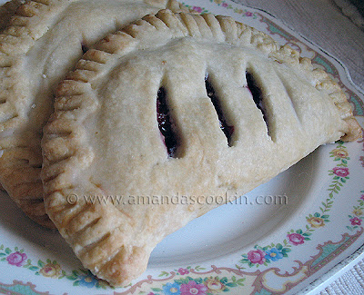 A close up photo of a cherry hand pie resting on a white plate.