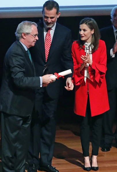 Queen Letizia wore a Zara Frilled Sleeve Coat and Roberto Verino Blouse, Carolina Herrera black-patent and suede pumps and carried Carolina Herrera Animal Print Clutch Bag