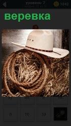 На сене лежит свернутая веревка и шляпа сверху, набор для пастуха