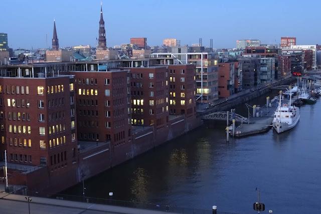 Seitenarm der Elbe mit Schiffsanleger und Bürotürmen mit Licht in Hamburg